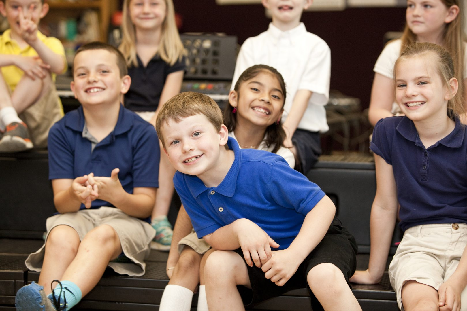 A group of elementary students smile for the camera