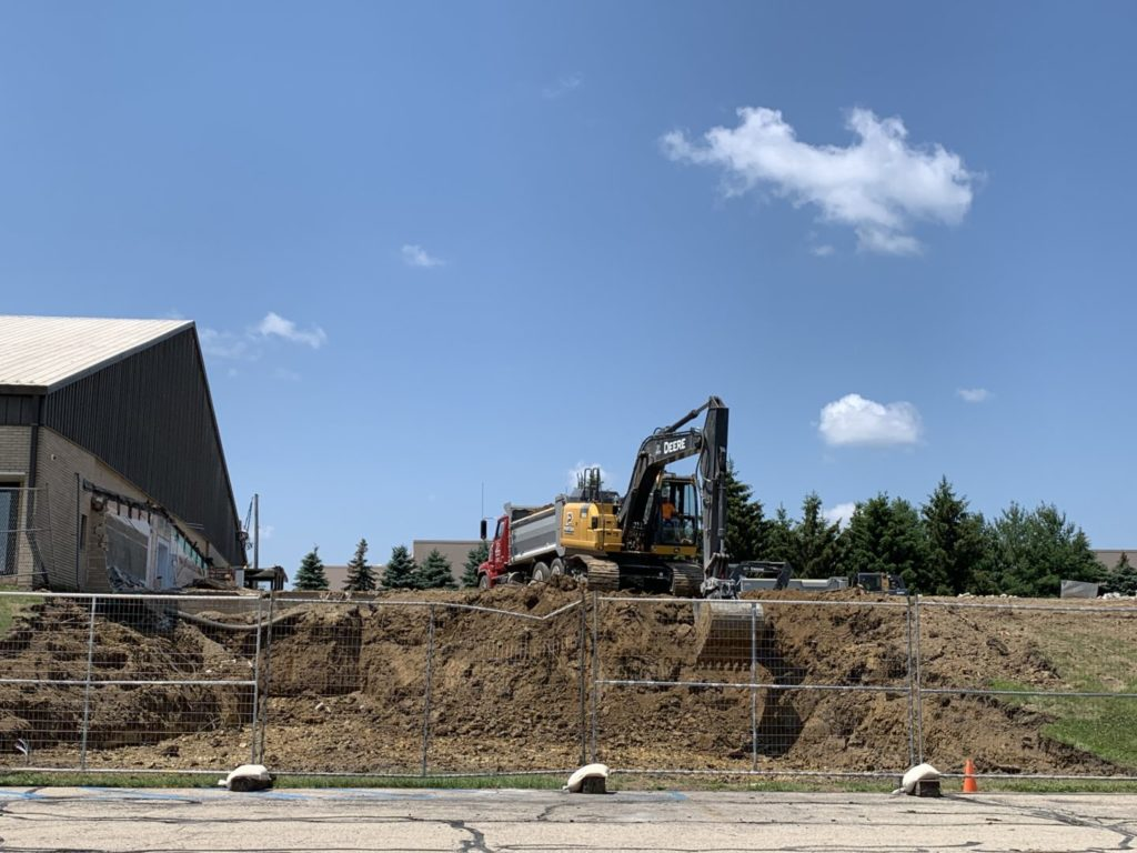 Excavation to create a parking lot-level entrance.